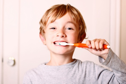 A young boy brushing his teeth with kid friendly toothpaste.