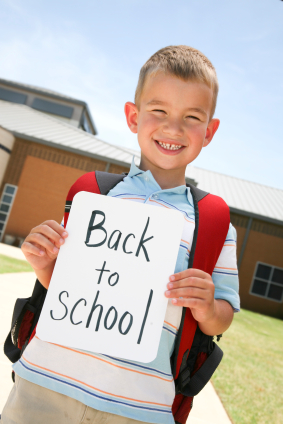 A young boy holding a back to school sign.