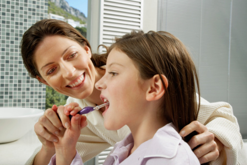 A Mother helping Daughter Brush Teeth