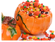 A bowl shaped like a pumpkin and full of candy.
